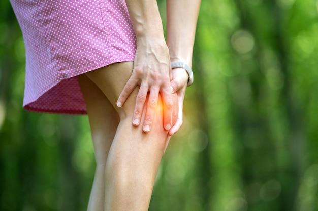 Kobieta Trzyma Kolano Z Rękami O Silnym Bólu. Premium Zdjęcia