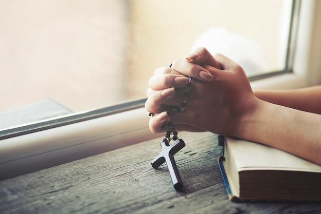 Kobieta Trzyma Krzyż Podczas Gdy Modli Się Premium Zdjęcia