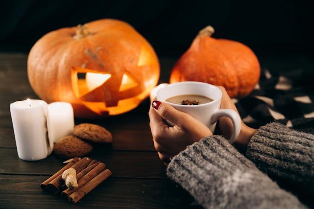 Kobieta Trzyma Kubek Gorącej Czekolady W Ramionach Przed Halloween Dynia Darmowe Zdjęcia