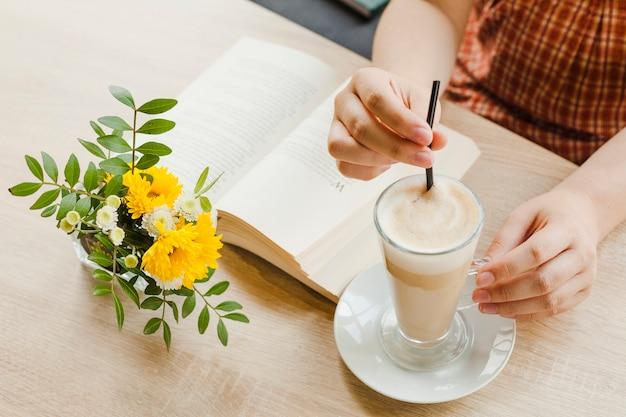 Kobieta trzyma kubek latte siedząc w kawiarni� Darmowe Zdjęcia