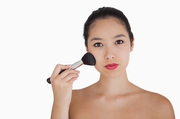 Kobieta Trzyma Muśnięcie Na Jej Twarz Premium Zdjęcia