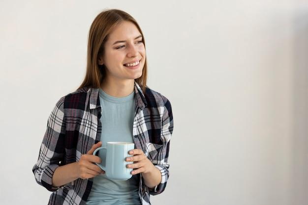 Kobieta trzyma niebieską filiżankę kawy Darmowe Zdjęcia