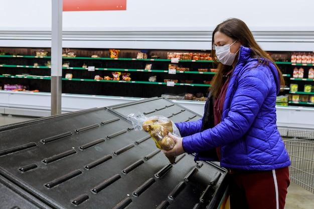 Kobieta Trzyma Ostatnią Torbę Grula Przy Supermarketem Z Pustymi Półkami Z Maską. Premium Zdjęcia