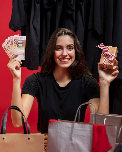 Kobieta Trzyma Pieniądze I Zapakowany Prezent Darmowe Zdjęcia