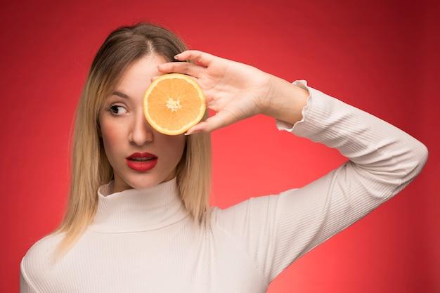 Kobieta trzyma plasterek pomarańczy nad jej okiem Darmowe Zdjęcia