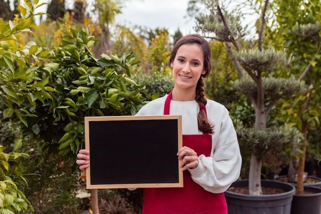 Kobieta Trzyma Pustego Blackboard W Ogródzie Darmowe Zdjęcia