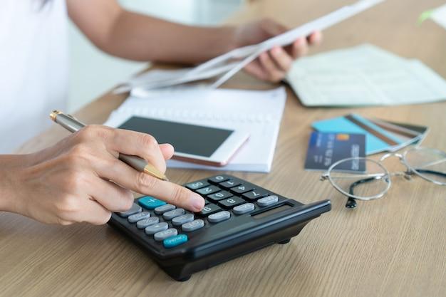 Kobieta Trzyma Rachunki I Używa Kalkulatora, Konta I Oszczędzania Pojęcie. Premium Zdjęcia