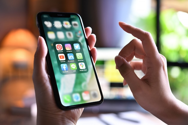 Kobieta Trzyma Smartphone Z Ikonami Ogólnospołeczni środki Na Ekranie W Domu Premium Zdjęcia