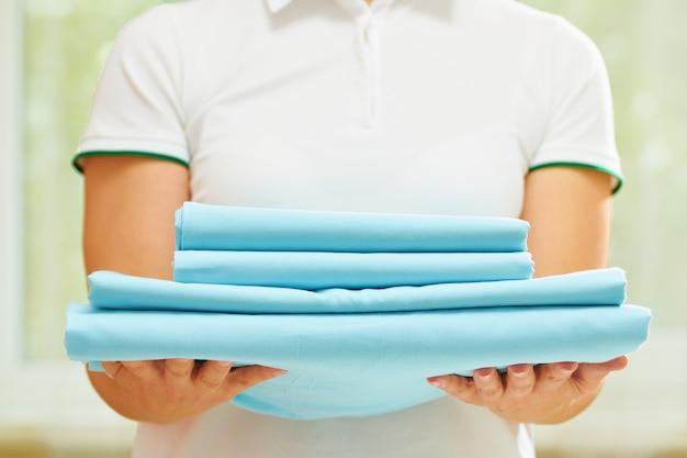 Kobieta Trzyma Stos Czystej Złożonej Niebieskiej Pościeli. Premium Zdjęcia