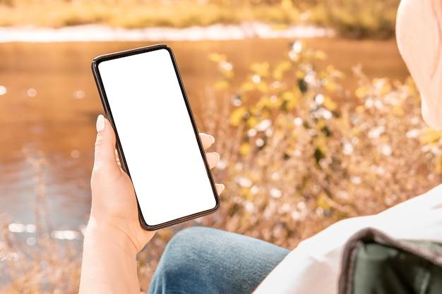 Kobieta Trzyma Telefon Z Pustym Ekranem Premium Zdjęcia