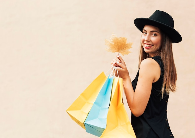 Kobieta Trzyma Torby Na Zakupy I Liść Z Miejsca Na Kopię Darmowe Zdjęcia