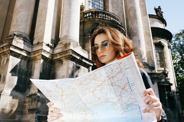 Kobieta trzyma turystyczną mapę w jej ręki pozyci przed starą katedrą Darmowe Zdjęcia
