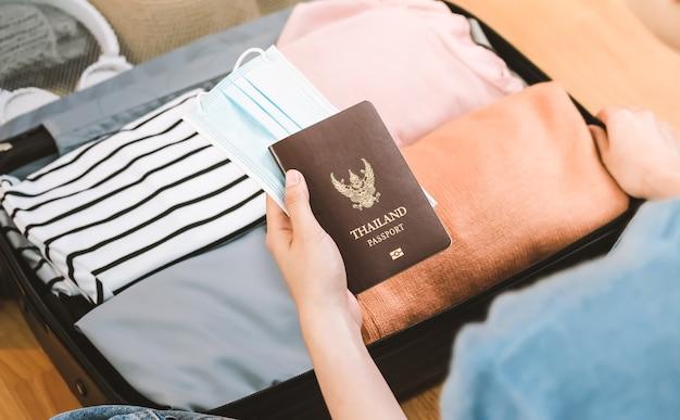 Kobieta Trzyma Ubrania I Trzyma Paszport Z Maską W Bagażu. Premium Zdjęcia