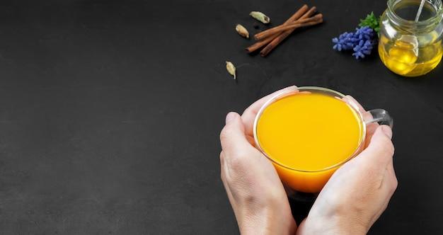 Kobieta Trzyma W Rękach Kubek Naturalnego Zdrowego Napoju Z Kurkumy I Przypraw Premium Zdjęcia