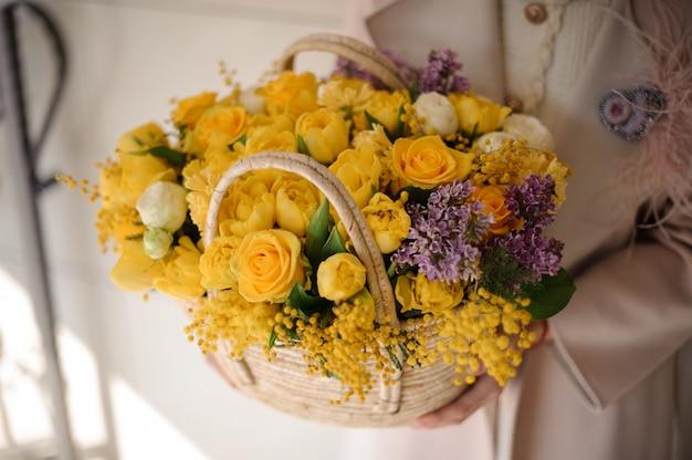 Kobieta trzyma wiosna kosz czuli żółci kwiaty Premium Zdjęcia