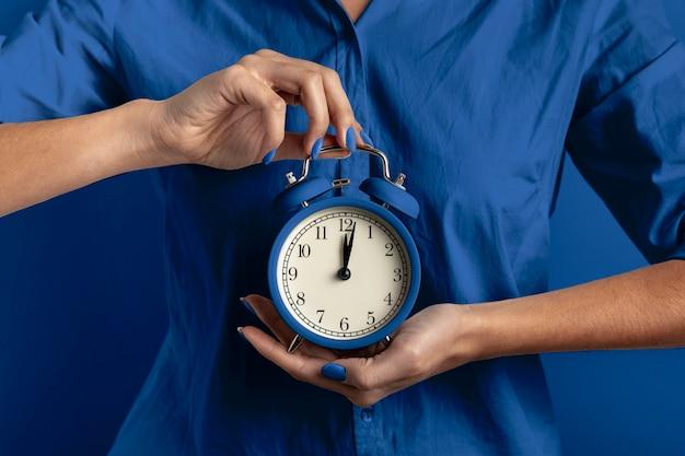Kobieta Trzyma Zegar O Klasycznym Niebieskim Kolorze Premium Zdjęcia