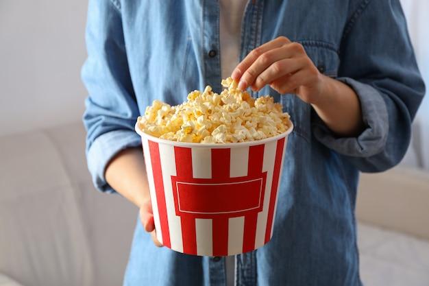 Kobieta Trzymać Wiadro Z Popcornem. Jedzenie Do Oglądania Filmów Premium Zdjęcia