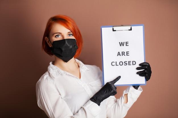 Kobieta Trzymająca Puste Miejsce Z Napisem Jesteśmy Zamknięci Wzywając Do Zaprzestania Rozprzestrzeniania Covid-19 Premium Zdjęcia