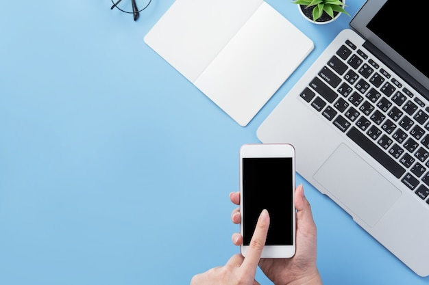 Kobieta Trzymająca Smartfon Z Minimalnym Niebieskim Biurkiem, Koncepcja Zakupów Online, Płatność Internetowa, Handel Elektroniczny, Miejsce Do Kopiowania, Układanie Na Płasko, Widok Z Góry, Makieta Premium Zdjęcia