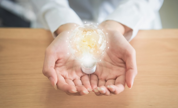 Kobieta trzymająca żarówkę z innowacją i kreatywnością to klucze do sukcesu. Premium Zdjęcia