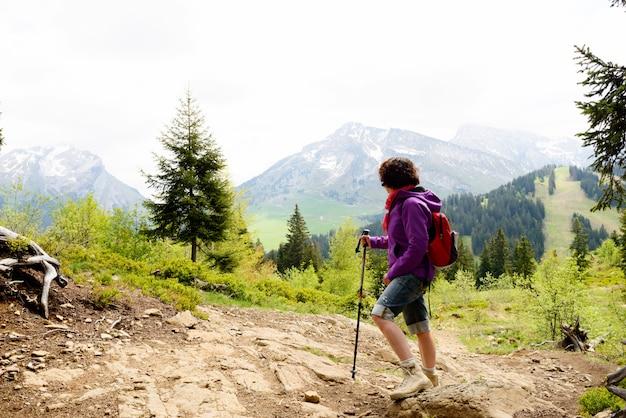 Kobieta turysta patrzy na szczyt góry Premium Zdjęcia