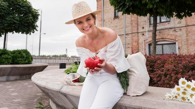 Kobieta Ubrana Na Biało Trzyma świeżego Pomidora Darmowe Zdjęcia