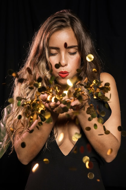 Kobieta ubrana na imprezę dmuchanie w złote konfetti Darmowe Zdjęcia