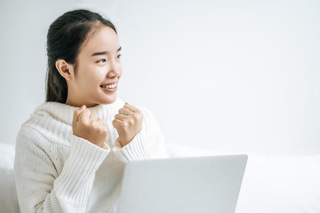 Kobieta Ubrana W Białą Koszulę Na łóżku I Szczęśliwie Grająca Na Laptopie. Darmowe Zdjęcia
