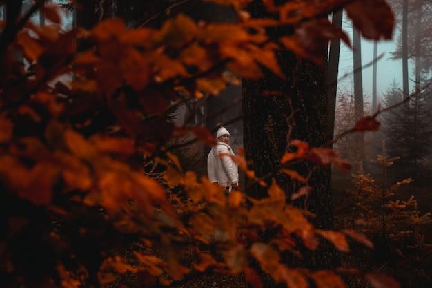 Kobieta Ubrana W Białą Kurtkę Stojącą W Pobliżu Drzewa W Lesie Darmowe Zdjęcia