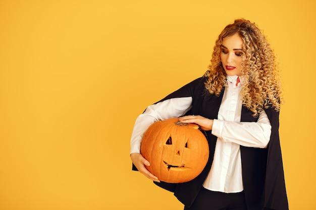 Kobieta Ubrana W Czarny Kostium. Pani Z Halloweenowym Makijażem. Dziewczyna Stojąca Na żółtym Tle. Darmowe Zdjęcia