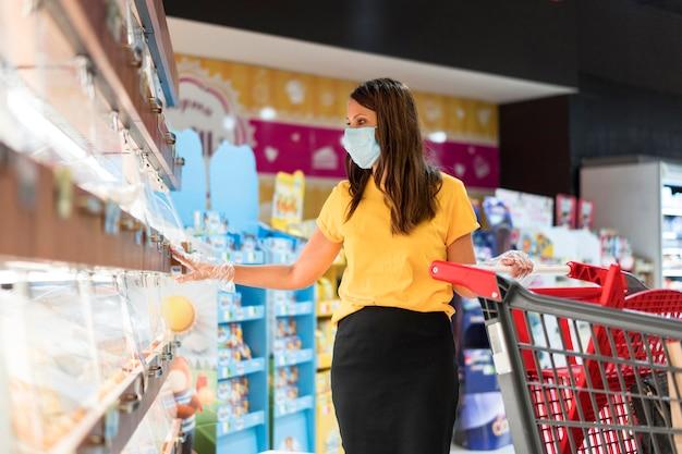 Kobieta Ubrana W Maskę Medyczną, Kupując W Sklepie Premium Zdjęcia