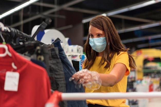 Kobieta Ubrana W Maskę Medyczną Patrząc Na Dżinsy Premium Zdjęcia