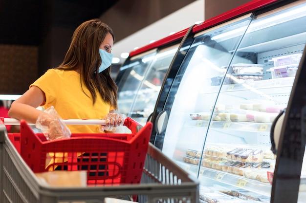 Kobieta Ubrana W Maskę Medyczną, Patrząc W Lodówkę Premium Zdjęcia