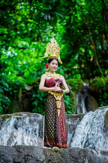 Kobieta ubrana w starożytną tajską sukienkę przy wodospadzie. Darmowe Zdjęcia