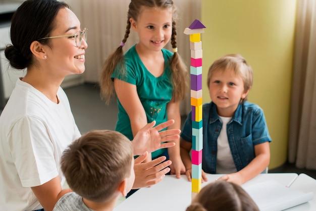 Kobieta Uczy Dzieci, Jak Bawić Się Kolorową Wieżą Darmowe Zdjęcia