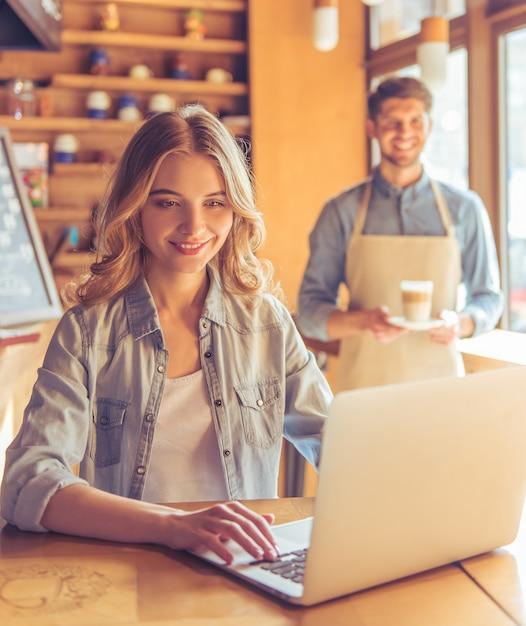 Kobieta Uśmiecha Się Podczas Pracy Z Laptopem W Kawiarni. Premium Zdjęcia