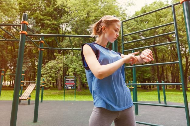 Kobieta używa aktywność tropiciela przy gym Premium Zdjęcia