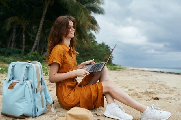 Kobieta Używa Laptop W Plaży Z Drzewkami Palmowymi Premium Zdjęcia