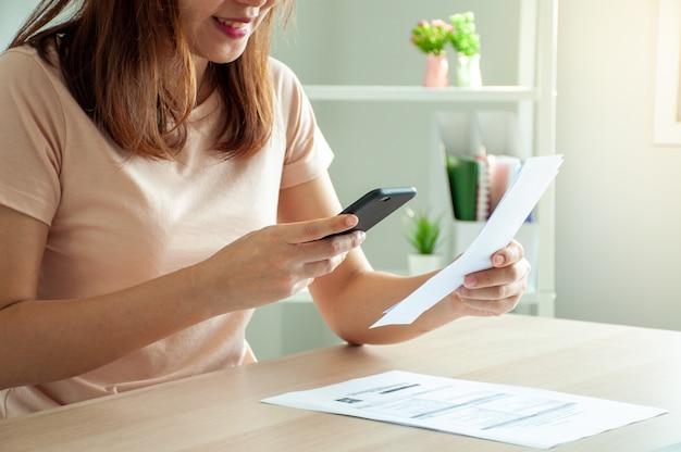 Kobieta Używa Smartfona Do Zeskanowania Kodu Kreskowego, Aby Płacić Miesięczne Rachunki Za Telefon Po Otrzymaniu Faktury Wysłanej Do Domu Premium Zdjęcia