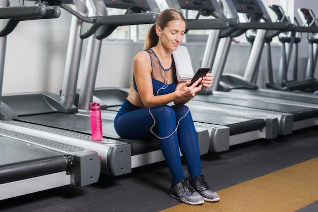 Kobieta używa smartphone w gym Darmowe Zdjęcia