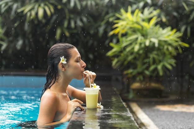 Kobieta w basenie z napojem owocowym Premium Zdjęcia