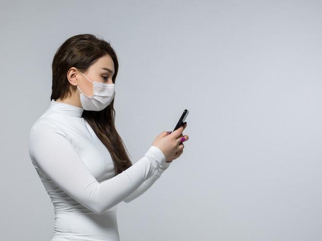 Kobieta W Białej Bezpłodnej Masce Patrząc Na Telefon Darmowe Zdjęcia
