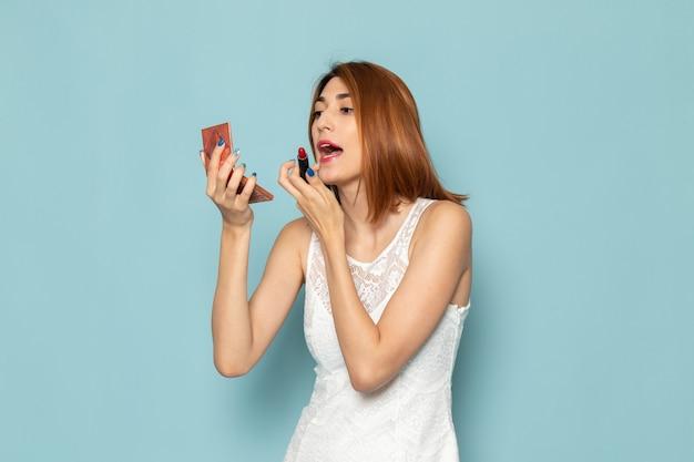 Kobieta W Białej Bluzce I Niebieskich Dżinsach Robi Makijaż Darmowe Zdjęcia