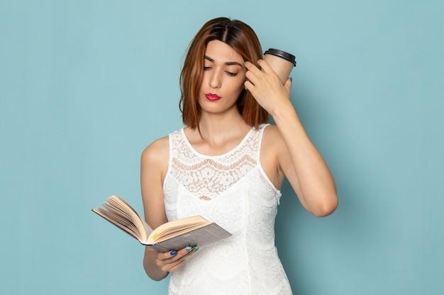 Kobieta W Białej Bluzce I Niebieskich Dżinsach, Trzymając Filiżankę Kawy I Książkę Darmowe Zdjęcia