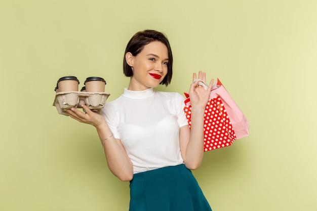 Kobieta W Białej Bluzce I Zielonej Spódnicy, Trzymając Pakiety Zakupów I Filiżanki Kawy Darmowe Zdjęcia