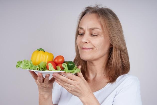 Kobieta W Białej Koszuli Trzyma Talerz Z Różnymi Warzywami Premium Zdjęcia
