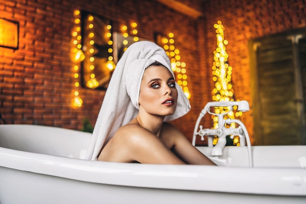 Kobieta W Białej Wannie Z Ręcznikiem Na Głowie Premium Zdjęcia