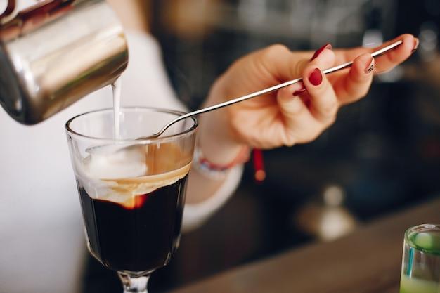 Kobieta w białym swetrze, wlewając mleko do deseru kawowego Darmowe Zdjęcia