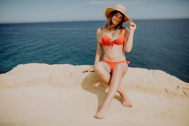 Kobieta W Bikini Siedzi Na Skraju Góry Darmowe Zdjęcia