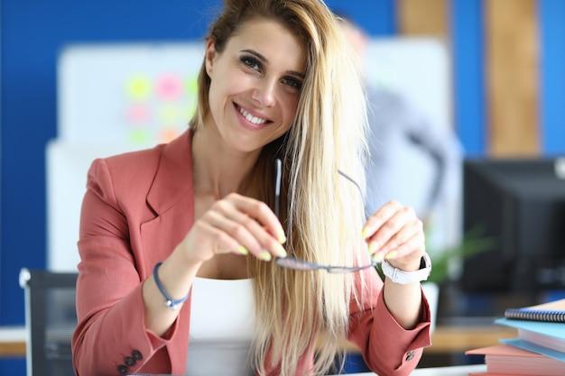 Kobieta W Biurze Siedzi Przy Stole, Trzyma Okulary W Dłoniach I Uśmiecha Się. Koncepcja Doradztwa Biznesowego I Zarządzania Premium Zdjęcia